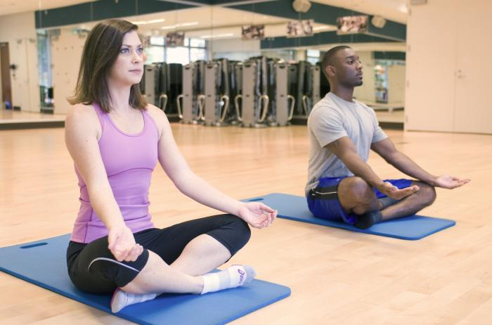 A woman and man meditate on yoga mats